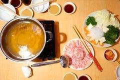未加工的猪肉切片、生气勃勃热菜在木表上和的汤 库存图片