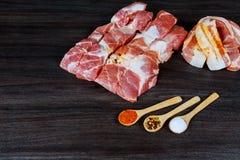 未加工的猪肉烟肉切片、更卤莽、香料、玫瑰色干胡椒和新鲜的迷迭香叶子在黑板岩上,关闭, 免版税库存图片