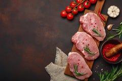 未加工的猪肉牛排片断在切板的有在生锈的褐色的西红柿、迷迭香、大蒜、胡椒、盐和香料灰浆的 免版税库存照片