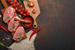 未加工的猪肉牛排片断在切板的有在生锈的西红柿、迷迭香、大蒜、胡椒、盐和香料灰浆的 免版税库存照片