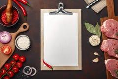 未加工的猪肉牛排片断在切板的用西红柿、迷迭香、大蒜、红辣椒、月桂叶、葱、盐和香料 免版税图库摄影