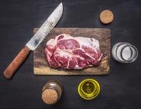 未加工的猪肉牛排用草本,肉的油刀子在切板木土气背景顶视图关闭 免版税库存照片