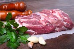 未加工的猪肉脖子剁肉用荷兰芹草本在石背景离开,香料的研磨机和大蒜 为烹调准备 库存照片