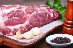 未加工的猪肉脖子剁肉用荷兰芹草本在石背景离开,香料的研磨机和大蒜 为烹调准备 免版税库存图片