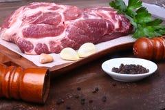 未加工的猪肉脖子剁肉用荷兰芹草本在石背景离开,香料的研磨机和大蒜 为烹调准备 免版税库存照片
