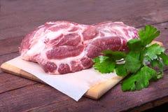 未加工的猪肉脖子剁肉用荷兰芹草本在石背景离开 为烹调准备 图库摄影