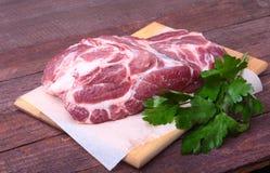 未加工的猪肉脖子剁肉用荷兰芹草本在石背景离开 为烹调准备 库存图片