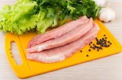 未加工的猪肉,绿色、在船上大蒜和胡椒片断  免版税库存图片