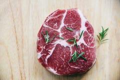 未加工的猪肉/新鲜的牛排准备好格栅用在木切板背景的香料迷迭香 图库摄影