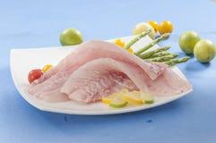 未加工的白色鱼内圆角用蕃茄和新牛至&柠檬切片 免版税库存照片
