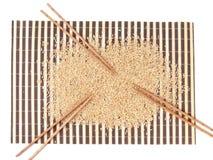 未加工的米和筷子在竹地毯 免版税库存照片