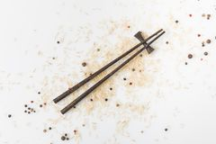未加工的米和香料溢出了与筷子的白色表面上 图库摄影