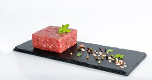 未加工的绞细牛肉片断在板岩板的与整个胡椒桃红色 免版税库存照片