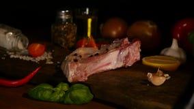 未加工的肉片特写镜头视图和辣椒与火焰在黑砧板 格栅牛排bbq火焰 影视素材