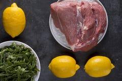 未加工的肉片用在黑石背景的柠檬 免版税库存照片