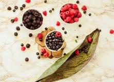 未加工的莓和蓝莓在白色杯子 白色大理石后面 免版税库存图片