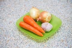 未加工的葱红萝卜和大蒜在塑料板材 免版税库存图片