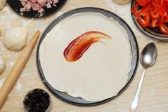 未加工的薄饼面团用调味汁和成份在木桌上 免版税图库摄影