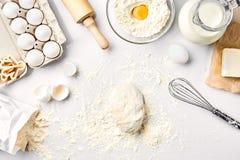 未加工的面团准备好揉在白色桌上 面包店成份,鸡蛋,面粉,黄油 做的曲奇饼形状 库存图片