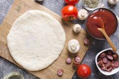 未加工的面团顶视图比萨的在切板和各种各样的成份它的 蕃茄,调味汁,蘑菇,油,草本,sausag 免版税库存照片