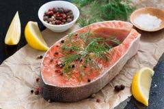 未加工的鲑鱼排、柠檬和香料为烹调做准备 免版税库存照片