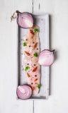 未加工的鲱鱼内圆角用在长方形板材的halfs红洋葱 库存照片
