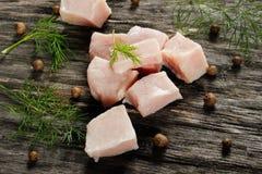 未加工的鸡内圆角切开了成立方体用木表面上的香料 免版税库存图片