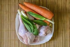 未加工的鸡腿用葱和红萝卜 免版税库存照片
