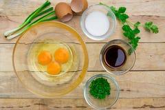 未加工的鸡蛋和成份在木背景 免版税库存图片