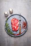 未加工的Ribeye牛排用香料和肉在灰色石板材分叉 库存图片