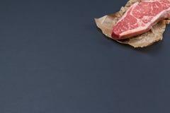 未加工的striploine纽约牛排在右角背景中 免版税图库摄影