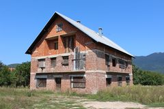 未完成放弃了有上的窗口和门的红砖郊区房子围拢与森林和山在背景中 图库摄影
