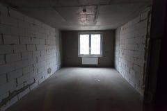 未完成的修造的内部,灰色室 在公寓的修理 准备在屋子里 免版税库存图片