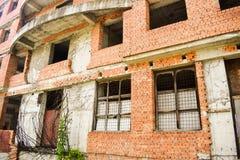 未完成的大厦在街市 与红砖和狂放的植被的被放弃的建筑项目 库存照片
