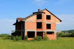未完成的没有门或窗口的砖家庭郊区房子 图库摄影