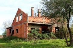 未完成的被放弃的砖房子包围与高植被 免版税库存照片