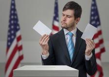 未定投票者在手上拿着信封在表决选票上 免版税图库摄影