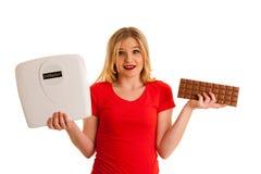 未定的妇女不定藏品标度和的巧克力是否 免版税库存照片