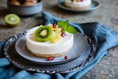 未成熟的微型乳酪蛋糕冠上了用菠萝、猕猴桃和石榴 库存照片