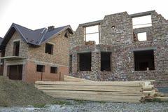 未来村庄建设中和堆石渣和堆在不完成的新的大砖房子前面的委员会有棕色s的 图库摄影