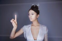 未来概念 年轻人相当亚裔妇女感人的数字式全息图 免版税库存照片