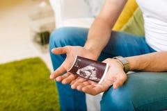 未来父亲拿着超声波图片 免版税库存图片