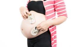 未来的婴孩的小鞋子孕妇的腹部的我 库存图片
