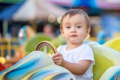 未来竞赛冠军画象:小孩孩子坐在旋转木马的一点明亮的汽车在有骄傲的面孔的主题乐园 免版税库存照片