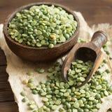 未煮过的在一个碗的绿色分裂豌豆有匙子的 库存图片