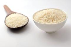 未煮过的米,茉莉花米,马里米,在木杓子的泰国茉莉花米,白色碗陶瓷在白色背景 库存照片