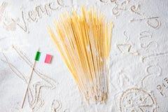 未煮过的面团意粉通心面和意大利旗子在被撒粉于的白色背景 食物旅行意大利烹调概念 免版税库存图片