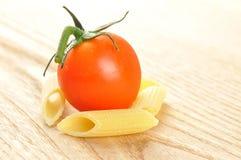 未煮过的penne意大利面食和蕃茄,特写镜头 免版税库存照片