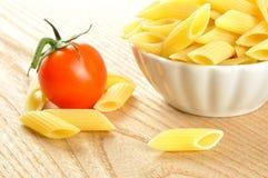 未煮过的penne意大利面食和蕃茄,特写镜头 库存图片