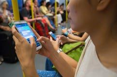 未知的人民乘地铁时使用手机,当旅行 库存图片